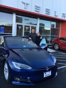 photo courtesy Rob White  White (l) with his wife and Tesla after buying the car.